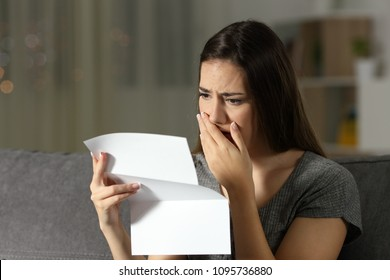 Sad woman complaining reading a letter in the night sitting on a couch in the living room at home