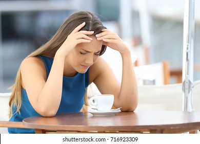 Sad woman complaining sitting in a coffee shop terrace