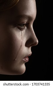 sad woman crying, looking aside on black background, closeup portrait, profile view