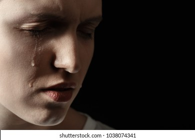 sad woman crying on black background with copy space, closeup portrait