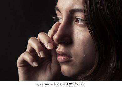sad woman crying on black background, closeup portrait