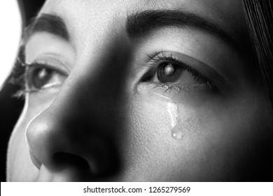 sad woman crying on black background, looking up, closeup portrait, monochrome