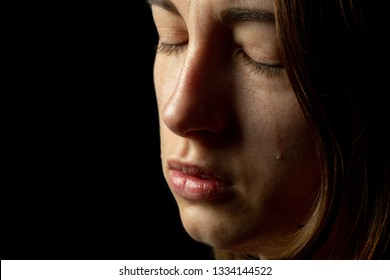 sad woman crying on black background, closeup portrait