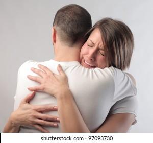 Sad woman crying on her husband's shoulder