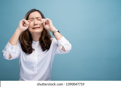 Sad woman crying and standing isolated on blue background