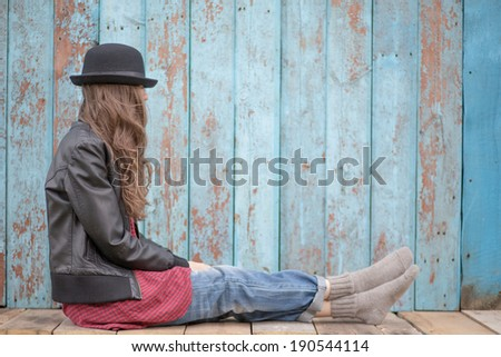 Sad woman deep in thought sitting over grunge wooden background. copy space