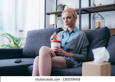 sad woman eating ice cream while siitng on couch and watching tv at home alone