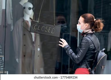 Traurige Frau am Eingang zu einem geschlossenen Bekleidungsgeschäft in einem Einkaufszentrum in einer Maske auf ihrem Gesicht. Geschlossener Laden, Geschäft wegen Quarantäne, Coronavirus, Covid-19. Schild Schließen an der Tür