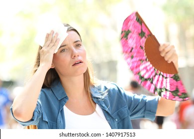 Sad woman fanning and sweating suffering a heat stroke on summer in the street
