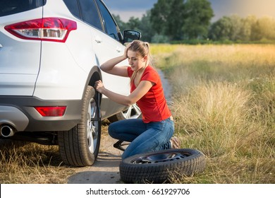 Sad woman got confused about changing flat tire in the field