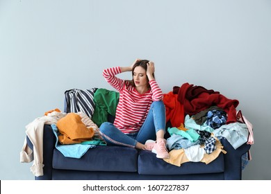 Sad woman with heap of clothes on sofa indoors