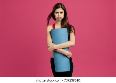 sad woman holding a fitness mat on a pink background