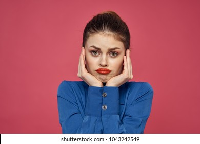 sad woman holding hands on face on pink background