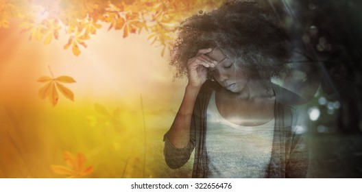 Sad woman holding her forehead with her hand against autumn scene