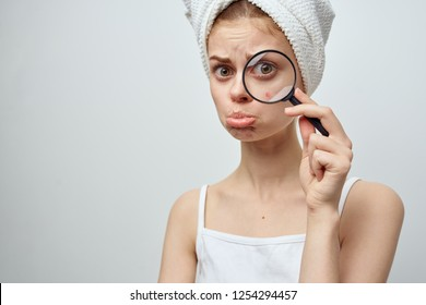 sad woman holds magnifier near pimple