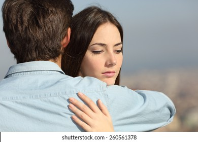 Sad woman hugging her boyfriend and looking down couple problems concept