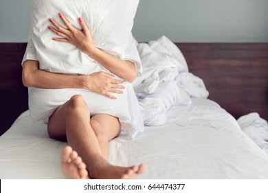 Sad woman hugging a pillow while and sitting in bed , Young Depressed Woman Sitting On Bed