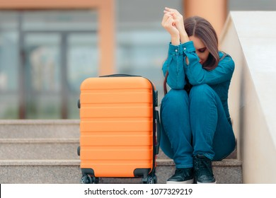 Sad Woman Leaving with Suitcase after Painful Break-up. Suffering girl sitting on Airport Station stars with her luggage