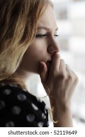 Sad woman loking at a window