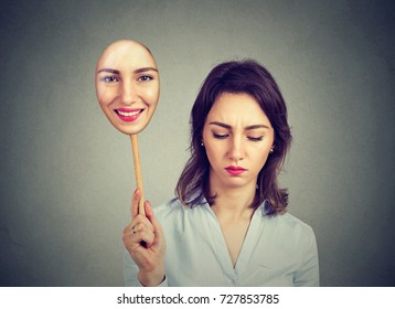 Sad woman looking down taking off happy mask of herself
