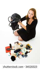Sad woman looking in her hand bag with it's contents laying on the floor