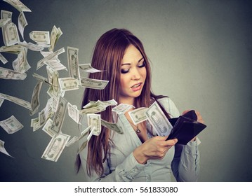 Sad woman looking at her wallet with money dollar banknotes flying out away