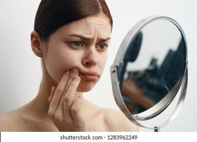 sad woman looking in the mirror