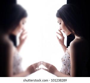 sad woman looking through the window.