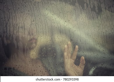 Sad woman looking through the window with rain drop in the car. Face of young female behind rain car window. Loneliness and depression concept. Psychology