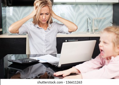 Sad woman looks at the bill. Female working at home. Child Makes moms work