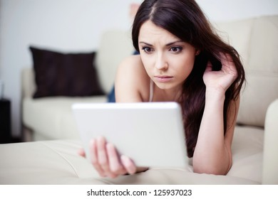 Sad woman lying on couch with tablet