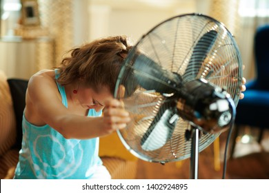 sad woman at modern home in sunny hot summer day showing victory gesture suffering from summer heat.