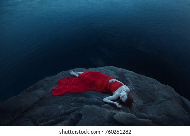A sad woman near the sea in evening