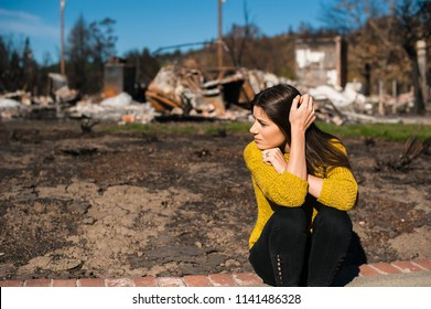 Sad woman owner holds his head by hand checking burnt out house and  yard after fire disaster, consequences of fire disaster accident. Ruins after fire disaster, loss and despair concept.