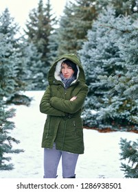 Sad woman is posing in winter forest, snowy fir trees.
