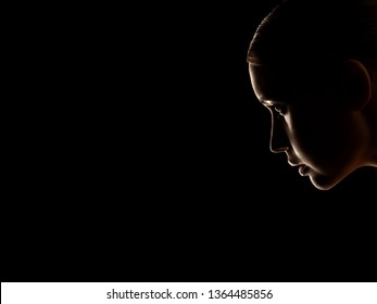 sad woman profile silhouette on black background with copy space, looking down