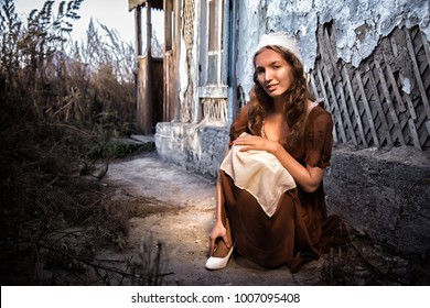 sad woman in a rustic dress sitting near old brick wall in old house and trying to dress a white shoe. Cinderella style