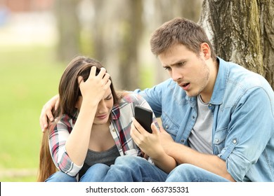 Sad woman shows negative message to a surprised friend sitting on the grass in a park