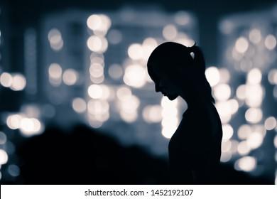 Sad woman silhouette walking city street at night.