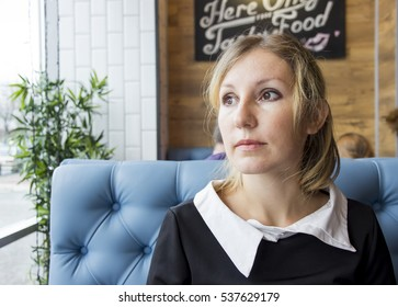 Sad woman sits in a cafe and looking out the window