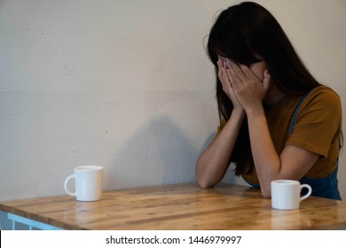Sad woman sitting alone. She took her hands off her face. Feeling depressed, frustrated, disappointed, discouraged or crying