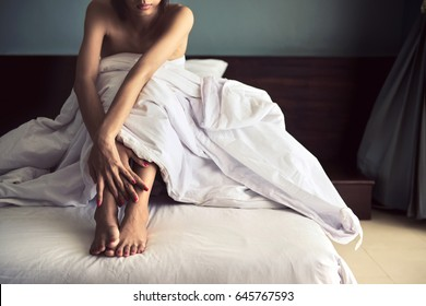 Sad woman sitting in bed , Depressed young victim woman sitting on the bed at home suffering from a severe depression ,  rape and crime concept