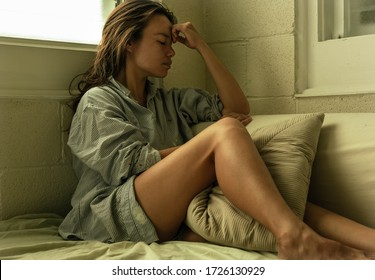 Sad woman sitting in bed at home thinking. Depression.