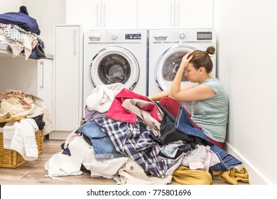 Sad woman sitting in laudry room with a pile of dirty clothes