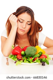 sad woman sitting near plate with vegetables and tired from diet