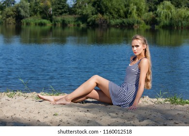 Sad woman sitting on the beach wearing mini dress