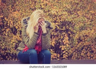 Sad woman sitting on bench in park during autumn weather hiding face in hand, feeling terrible depressed.