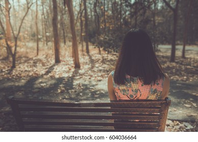 Sad woman sitting on the bench from back angle in the park vintage style,She passed the story lot worse.