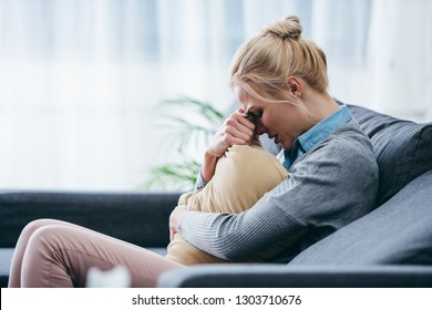 sad woman sitting on couch, crying and holding pillow at home