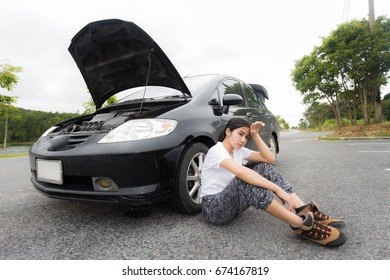 Sad woman sitting on the countryside road with broken car